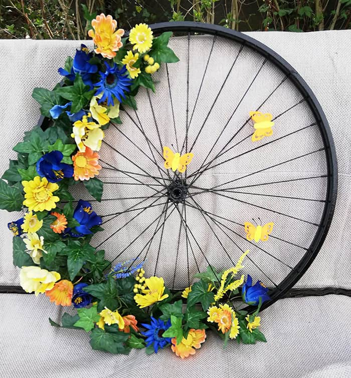 large easter wreath with flowers and wheel